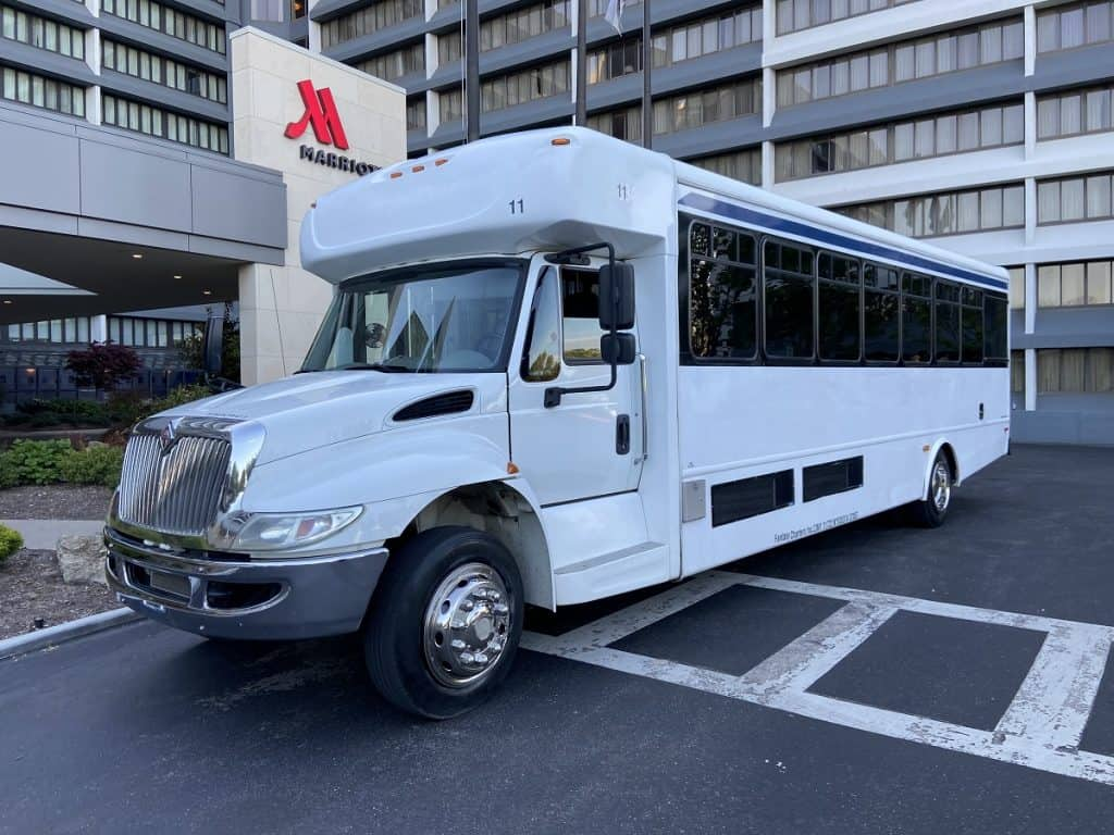 front and side of a white charter bus in front of a hotel
